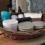 Στρογγυλό καλαθάκι με προϊόντα σώματος Το καλάθι περιλαμβάνει προϊόντα από τη σειρά περιποίησης σώματος.  Απολεπιστική κρέμα σώματος, body butter, μάσκα σώματος, λάδι για την άμεση θεραπεία των κιτρινισμένων και σπασμένων νυχιών, σαπούνια σώματος.